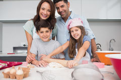 Portrait of a family of four preparing cookies in kitchen Stock Photography