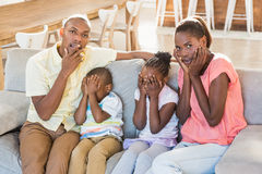 Portrait of a family of four watching tv. In living room Royalty Free Stock Images