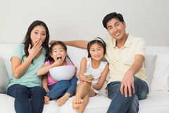 Portrait of a family of four watching tv in living room. Portrait of a happy family of four watching tv in the living room at home Royalty Free Stock Photo