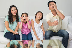 Portrait of a family of four watching tv in living room Stock Images