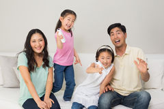 Portrait of a family of four watching tv in living room. Portrait of a family of four watching tv in the living room at home Stock Image