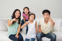 Portrait of a family of four watching tv in living room. Portrait of a family of four watching tv in the living room at home Stock Photography