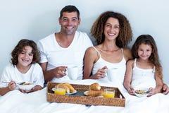 Portrait of family having breakfast in bed Stock Image