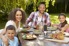 Portrait Of Family At Home Eating Outdoor Meal In Garden stock image