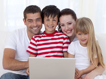 Portrait of family at home using a laptop. Portrait of happy family at home using a laptop royalty free stock images