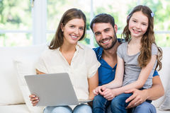 Portrait of family with laptop sitting on sofa Stock Photography