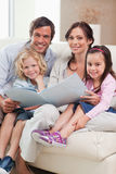 Portrait of a family looking at a photo album royalty free stock photography