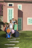 Portrait Of Family With Luggage In Front Of House stock photo
