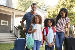 Portrait Of Family With Luggage Leaving House For Vacation stock photography
