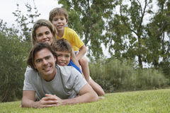 Portrait Of Family Lying On Top Of Each Other In Park Stock Images