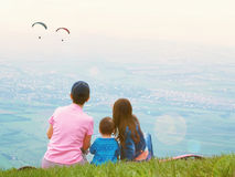Portrait of family mother brother and sister together sitting in nature look at paraglider Royalty Free Stock Photos