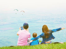 Portrait of family mother brother and sister together sitting in nature look at paraglider stock image