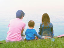 Portrait of family mother, brother and sister together sitting in nature Royalty Free Stock Image
