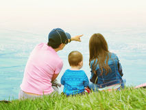Portrait of family mother, brother and sister together sitting in nature Royalty Free Stock Images