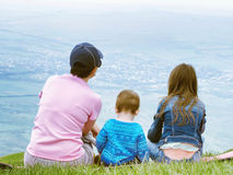 Portrait of family mother, brother and sister together sitting in nature Royalty Free Stock Photos