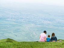 Portrait of family mother, brother and sister together sitting in nature stock photography