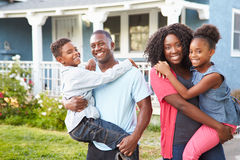 Portrait Of Family Outside Suburban Home. With Parents Holding Children Smiling stock images