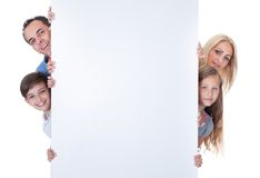 Portrait Of Family Peeping Behind Blank Board. Portrait Of Family With Two Children Peeping Behind Blank Board On White Background Royalty Free Stock Photos