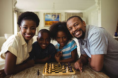 Portrait of family playing chess together at home in the living room Royalty Free Stock Photo
