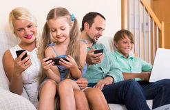 Portrait of  family playing with gadgets at home Royalty Free Stock Photos