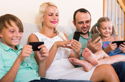 Portrait of  family playing with gadgets at home. Portrait of positive family playing with gadgets at home Royalty Free Stock Photos