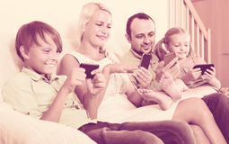 Portrait of  family playing with gadgets at home Royalty Free Stock Photography