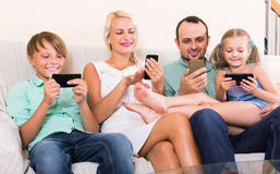 Portrait of  family playing with gadgets at home Royalty Free Stock Images
