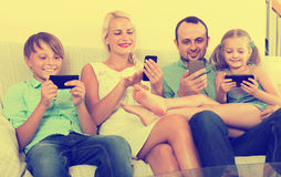Portrait of  family playing with gadgets at home Stock Photo
