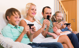 Portrait of family playing with gadgets at home. Portrait of positive russian family playing with gadgets at home stock images