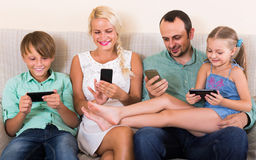 Portrait of  family playing with gadgets at home Stock Photos