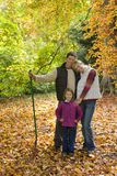 Portrait of family with rake standing in autumn leaves Stock Photos
