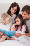 Portrait of a family reading a book Royalty Free Stock Photo