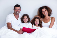 Portrait of family reading book together on bed Royalty Free Stock Images