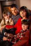 Portrait Of Family Relaxing On Sofa. By Cosy Log Fire Royalty Free Stock Image