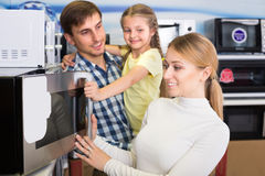 Portrait of family selecting microwave royalty free stock image