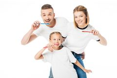Portrait of family in similar clothing brushing teeth. Isolated on white royalty free stock images