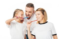 Portrait of family in similar clothing brushing teeth. Isolated on white royalty free stock photo