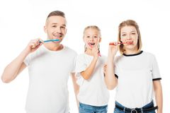 Portrait of family in similar clothing brushing teeth. Isolated on white royalty free stock photos