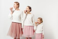 Portrait of family in similar clothing eating sweet doughnuts. On grey royalty free stock images