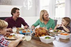Portrait Of Family Sitting Around Table Eating Meal At Home Stock Images