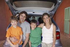 Portrait Of Family Sitting On Car Tailgate Stock Photo