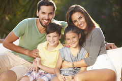 Portrait Of Family Sitting In Garden Together Stock Photo