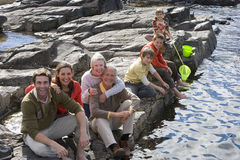 Portrait of family sitting on rock by river royalty free stock photography