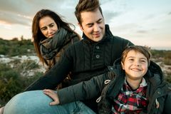 Portrait of a family smiling and happy in the countryside. Marriage with one child in the field stock image