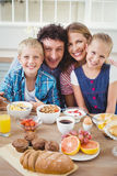 Portrait of family smiling while having breakfast Stock Photography