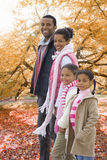 Portrait of family standing in park with autumn leaves Stock Image