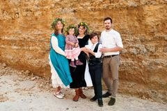 Portrait of a family of three generations in vintage rustic retro clothes and wreaths against a background of wall of yellow sand stock photography