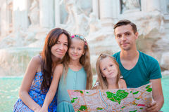 Portrait of family with touristic map near Fontana di Trevi, Rome, Italy. Happy parents and kids enjoy italian vacation stock photography