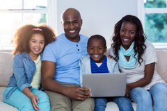 Portrait of family using laptop. At home stock photo