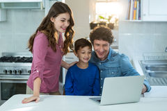 Portrait of family using laptop. At kitchen stock photo